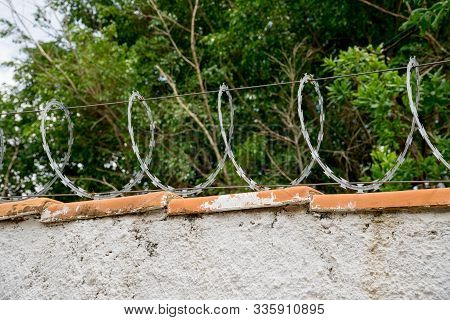 Barbwire Sitting On Top Of A Tall Fence For Extra Protection