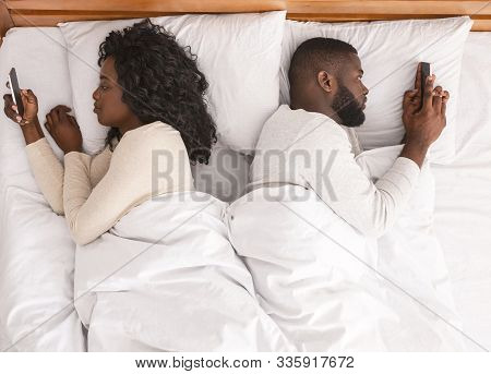Communication And Relationship Problem. Black Couple Using Smartphones In Bed, Lying Back To Back, I