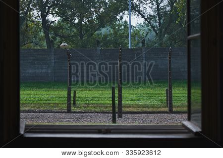 Auschwitz, Poland - July 27, 2018 View Through The Window From The Barack To The Fence Made With The