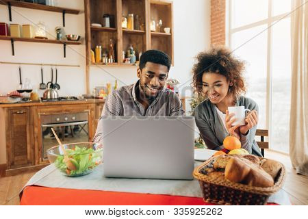 Happy African-american Couple Using Laptop At Kitchen, Planning Wedding And Honeymoon., Panorama, Co