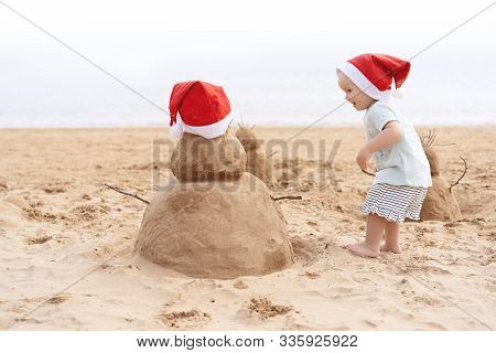 Little Child In Red Santa Hat With Sand Snowman On Beach.