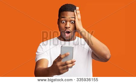 Bad News. Portrait Of Shocked Scared Black Man Looking At Phone Seeing Terrible Message, Nervous Rea