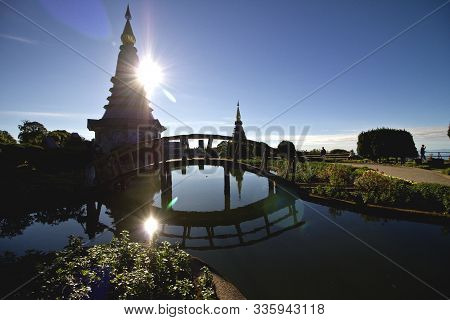 Sun Peeking Out From Behind One Of The Twin Pagodas In Doi Inthanon