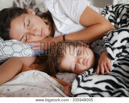 The Baby Sleeps With Mom In Bed. Cute Boy And His Mother Lying On The Sofa In The Bedroom, Sleep Pea