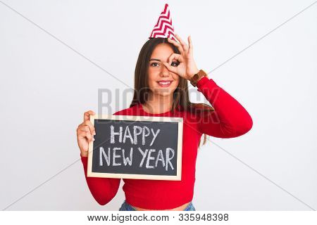 Beautiful girl wearing fanny party hat holding blackboard over isolated white background with happy face smiling doing ok sign with hand on eye looking through fingers