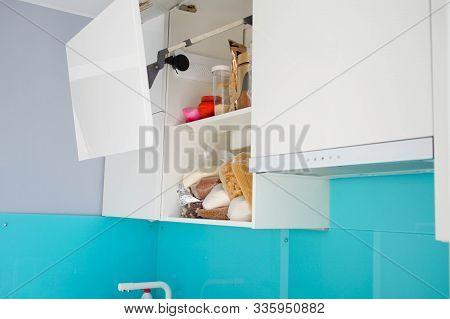 Unorganized Storage Of Cereals In The Kitchen Cabinet. Modern White Kitchen Without Handles.