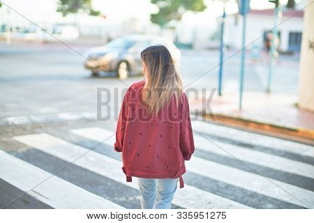 Young beautiful woman wearing red jacket walking over crosswalk on backview at the town street