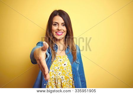 Young beautiful woman standing over yellow isolated background smiling friendly offering handshake as greeting and welcoming. Successful business.