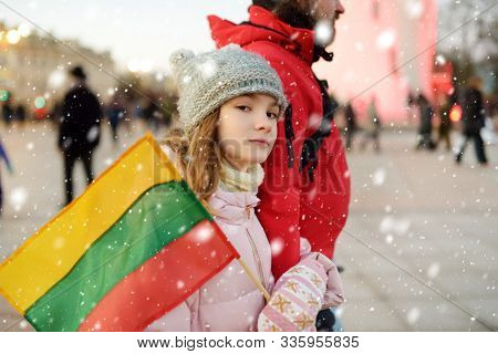 Father And Daughter Holding Tricolor Lithuanian Flag On Lithuanian Independence Day. Family Celebrat