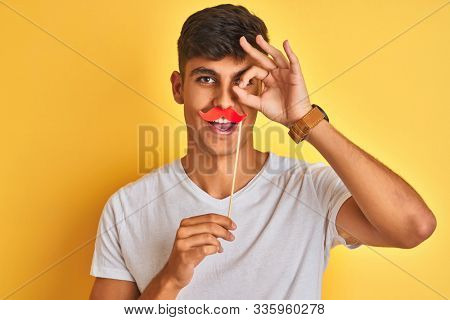 Young indian man holding fanny mustache standing over isolated yellow background with happy face smiling doing ok sign with hand on eye looking through fingers