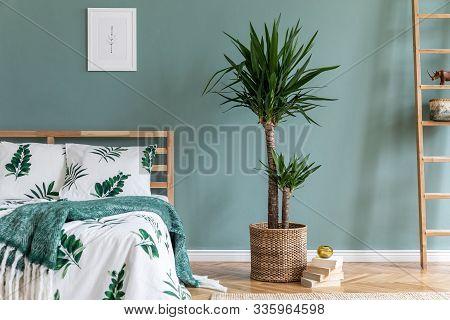Stylish Interior Design Of Bedroom With Wooden Bed, Mock Up Poster Frame, Rattan Ladder, Tropical Pl
