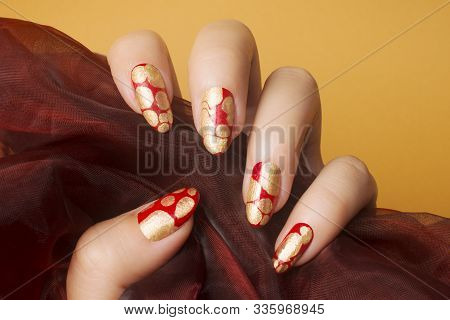 Female Hand With Red Gold Nails On Orange Background, Nail Care And Manicure Concept.