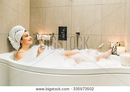 Happy Beautiful Woman Relaxing In A Bubble Bath Tub, Holding Glass Of Wine, White Towel On The Head