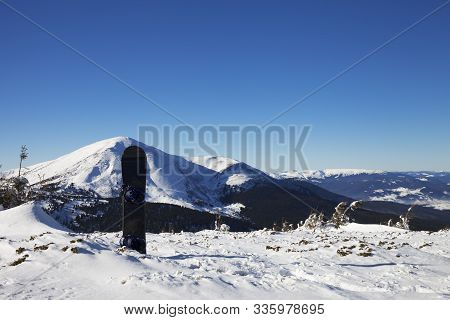 Snowboard In Snow And Snow-capped Mountains At Sunny Cold Morning. Mount Petros (chornohora) At Back