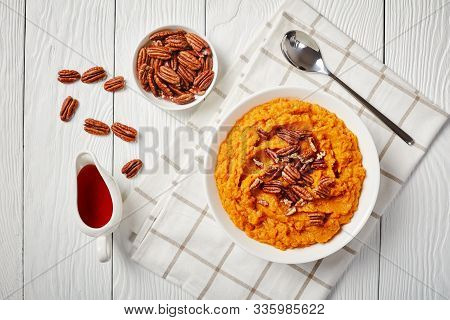 Delicious Sweet Potato Mash Topped With Pecan Nuts In A Bowl. Maple Syrup In A White Sauceboat On A