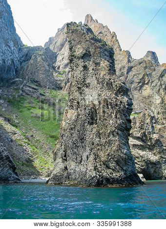 A Lone Vertical Rock Protrudes From The Sea Against The Backdrop Of The Crimean Mountains Of The Kar