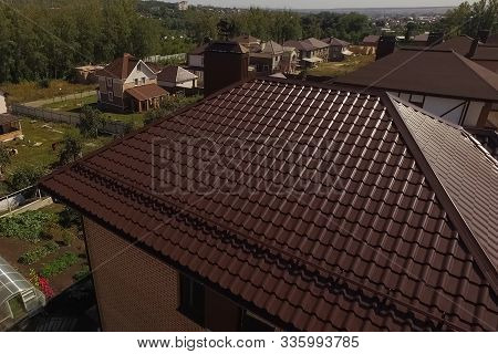 Brown Roof Of The House Made Of Metal. House In The Village. Modern Roof Made Of Metal. Corrugated M