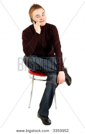 Handsome Guy Speaks By Mobile Sitting On A Chair