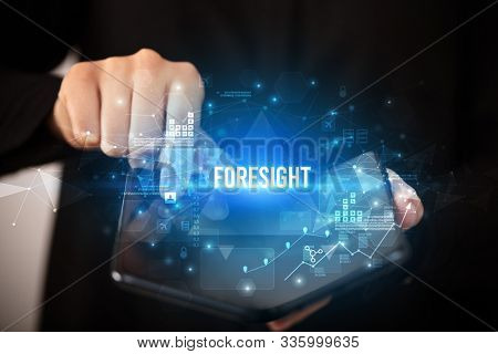 Businessman holding a foldable smartphone with FORESIGHT inscription, business concept poster