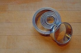 A Set Of Metal Pastry Rings In Various Sizes Rest On A Wood Cutting Board