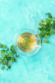 Mint Tea Cup, Top Shot On A Vibrant Turquoise Background With Fresh Mint Leaves And A Place For Text