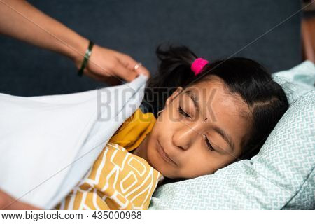 Mother Covering Child With Blanket While Kid Sleeping On Sofa - Concept Of Motherhood, Love Of Mothe