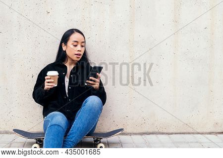 Young Asian Woman Typing On A Phone Sitting Outdoors On Her Skateboard Leaning Against A Concrete Wa