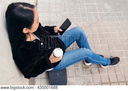 Unrecognizable Asian Girl Typing On A Phone Sitting Outdoors On Her Skateboard Leaning Against A Con