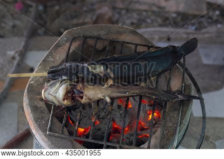 Grilled Batrachian Walking Catfish Or Airbreathing Catfish On Iron Grate Vintage Charcoal Stove.