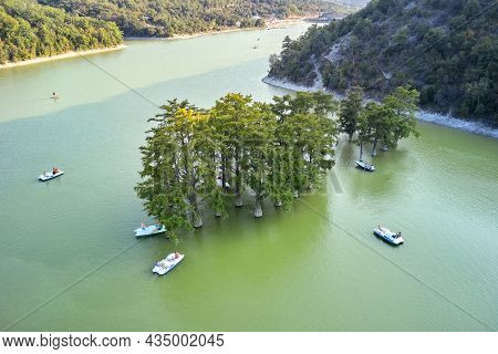 A Lake In The Mountains With A Grove Of Swamp Cypresses. Catamarans And Boats With Tourists Float On