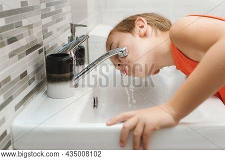 Boy Washing Face In The Bathroom. Morning Hygiene. Preteen Boy Is Washed In A Wash Basin. Healthy Ch