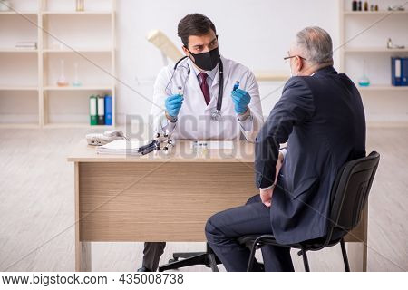Old businessman visiting young male doctor in vaccination concep