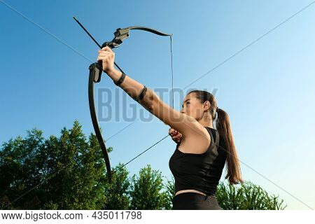 Woman With Bow And Arrow Practicing Archery Outdoors, Low Angle View