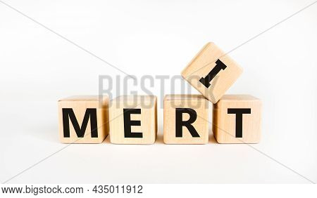Merit Symbol. The Concept Word 'merit' On Wooden Cubes On A Beautiful White Table. White Background.