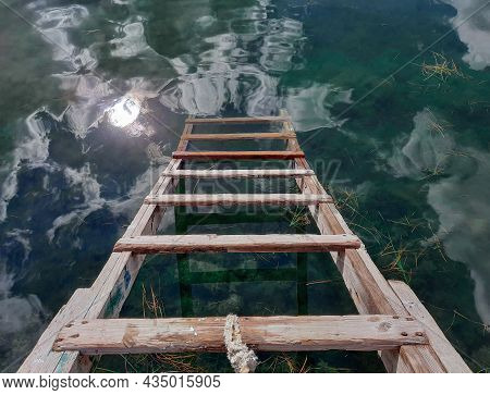 An Old Wooden Staircase Leads To Clear Water. Grass Floats On The Clear Water.