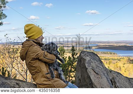 Young Woman In Brown Jacket Sitting With Fluufy Gray Dog In Arms On Rock And Looking At Beautiful Au