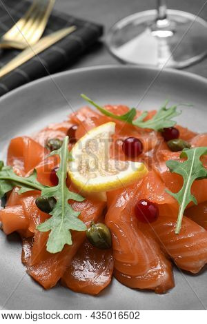 Salmon Carpaccio With Capers, Cranberries, Arugula And Lemon On Plate, Closeup
