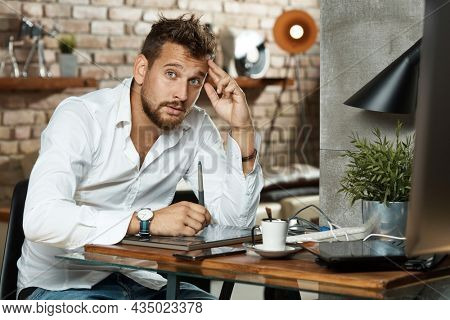 Happy young man working from home online. Graphic artist or designer sitting at desk using drawing tablet and laptop computer and teleworking in home office.