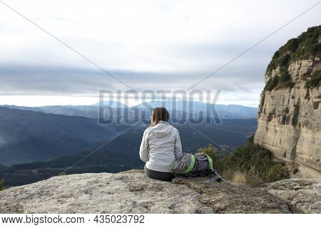 Back View Portrait Of A Trekker Sitting In A Cliff Contemplating