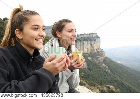 Two Happy Trekkers Drinking Coffee And Contemplating In A Cliff