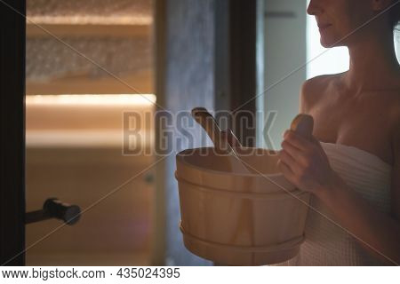 Real, authentic sauna moment. Woman sweating in hot sauna, holding sauna bucket making steam.