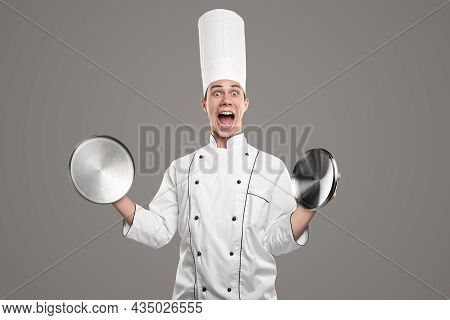 Funny Young Male Chef In White Uniform And Hat Looking At Camera With Astonished Grimace While Holdi