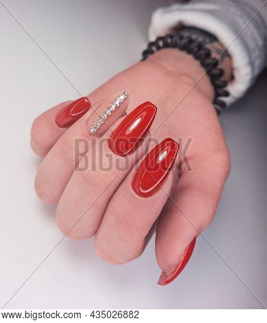 Bright Red Gel Polish On Long Nails With Beige Design And Stripes Of Rhinestones. An Attractive Mani