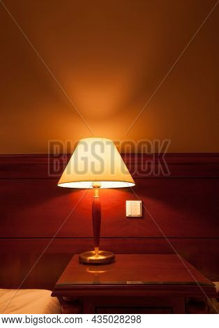 An elegant, classic bed side lamp in a cosy room. An illuminated lamp with white shade spreading a soft ambient light.