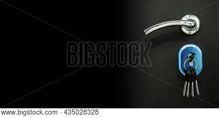 Black Dark Banner With Silver Door Handle And Bunch Of Keys Inserted Into Keyhole. Concept Of Sellin