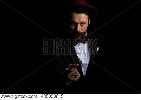 young businessman pointing at the camera with a tough attitude and wearing a burgundy hat
