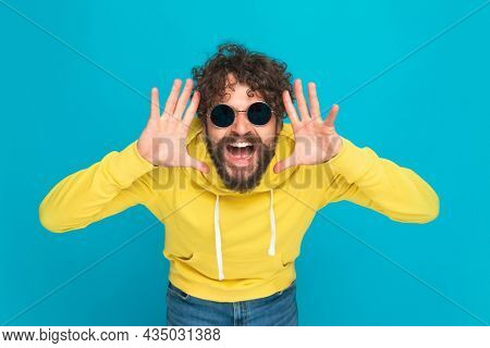 excited young guy in yellow hoodie making funny faces, laughing and having fun while posing against blue background in studio