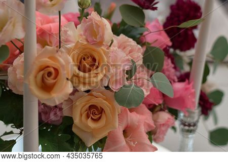 White Tablecloths With Clear Vases And Colourful Flowers Arrangements. Golden Colored Plates, Peavh