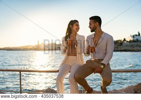 Delighted Loving Ethnic Couple In Trendy Outfits Sitting On Railing On Promenade And Drinking Refres