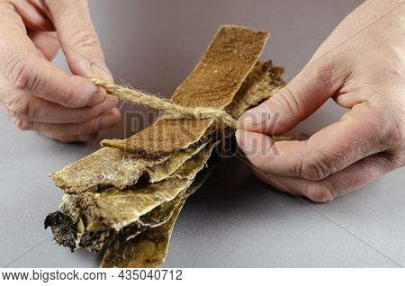 Two Hands Tie Twine To Dog Treats. Long Dried Plates Of Beef Stomach. Beef Tripe. Close-up. Selectiv